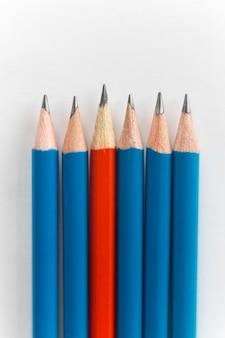 Lápices simples, uno rojo entre el azul