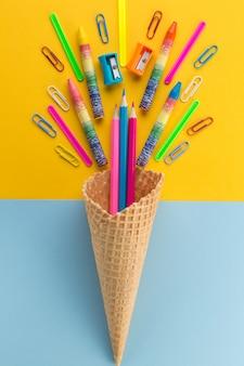 Lápices y sujetapapeles en cono de helado de gofres.