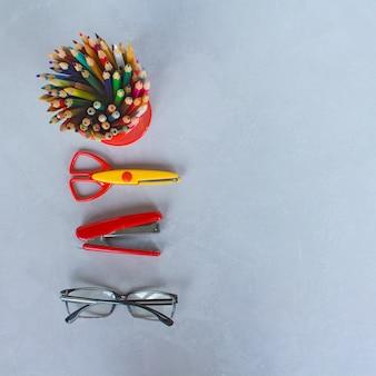 Lápices, tijeras, papelería, fondo gris.