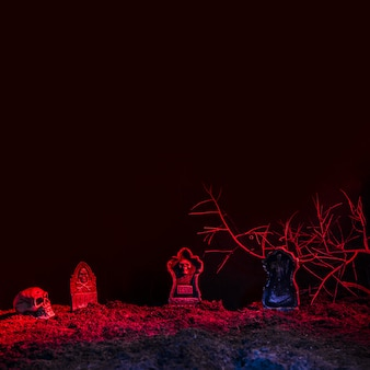 Lápidas y cráneo iluminado por luz roja en el suelo