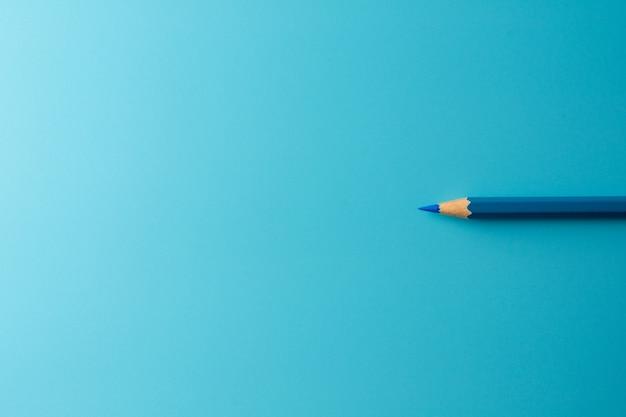 Lápiz azul del creyón en fondo del papel azul. - concepto de negocio.