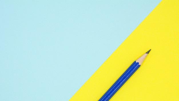 Lápiz azul sobre papel azul y amarillo.