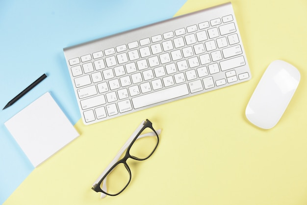 Lápiz; bloc de notas adhesivo; los anteojos; teclado y ratón inalámbricos sobre fondo azul y amarillo.