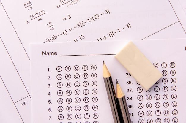 Lápiz y borrador en hojas de respuestas o formulario de prueba estandarizado con respuestas burbujeadas.