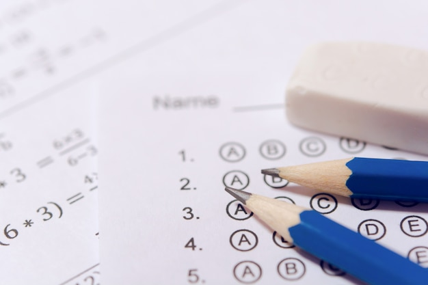 Lápiz y borrador en hojas de respuestas o formulario de prueba estandarizado con respuestas burbujeadas