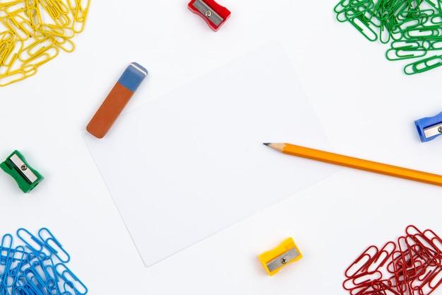 Lápiz, borrador, sacapuntas, clips de papel se encuentran en diferentes ángulos de la hoja sobre un fondo blanco. imagen de héroe y espacio de copia.