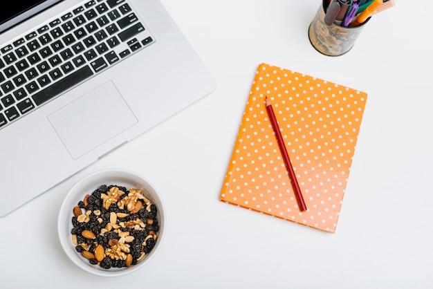Lápiz colorido; cuaderno; comida de la tuerca y computadora portátil en el fondo blanco