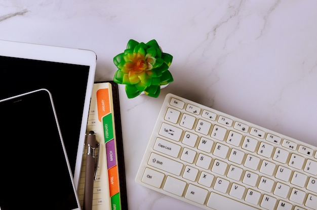 Lápiz de conceptos de planificación en el calendario semanal del cuaderno con el teléfono inteligente y el teclado