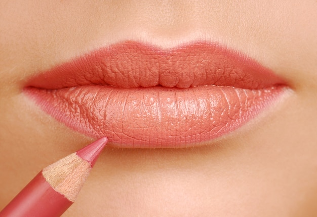 Lápiz cosmético de lápiz labial rojo. herramienta de maquillaje. labios de mujer de cerca