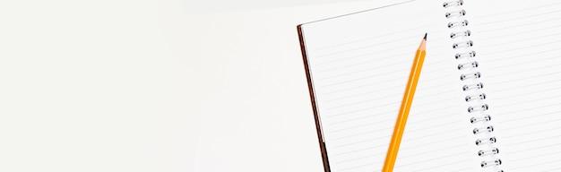 Lápiz y cuaderno aislado sobre un fondo blanco