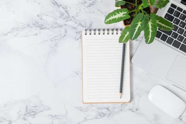 Lápiz en el cuaderno en blanco con la computadora portátil y el mouse en el fondo de la mesa de mármol, vista superior y espacio de copia