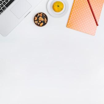 Lápiz; cuaderno; comida de nueces; computadora portátil y frutas cítricas en el fondo blanco