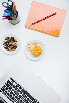 Lápiz; cuaderno; comida de nueces; ordenador portátil y naranja en la superficie blanca