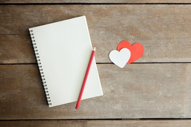Un lápiz en un cuaderno y un corazón rojo con luz matutina en tono vintage