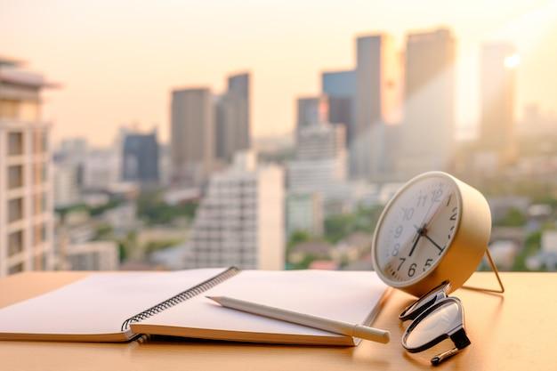 El lápiz en el cuaderno y las lentes del reloj del alam con la luz de oro borran el fondo de la puesta del sol.