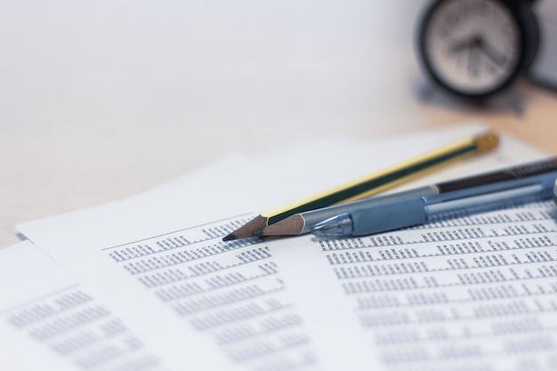 Lápiz e informe financiero sobre mesa con fondo de reloj