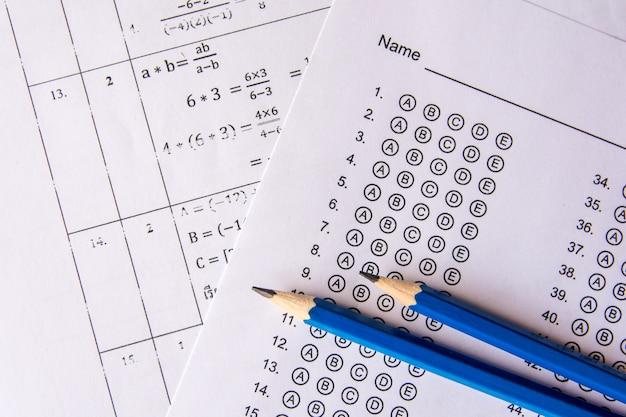 Lápiz en hojas de respuestas o formulario de prueba estandarizado con respuestas burbujeadas. hoja de respuesta de opción múltiple