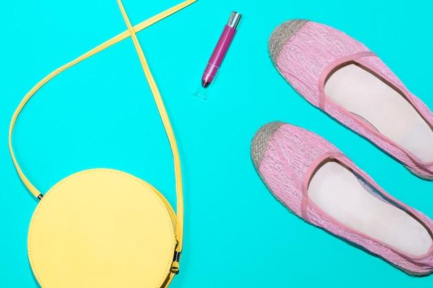 Lápiz labial, bolso y zapatos sobre fondo azul.