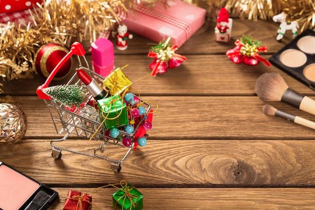 Lápiz labial en carrito de compras, pincel de maquillaje y adornos navideños en madera para fondo de navidad