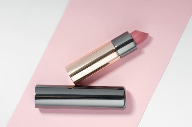 Lápiz labial de color rosa dorado y cromo sobre fondo rosa y blanco