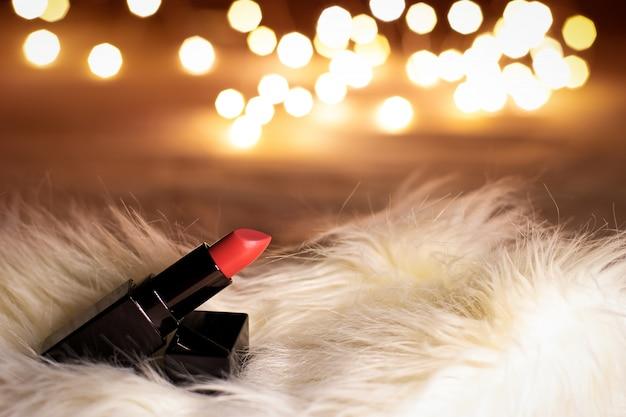 Lápiz labial de color rosa rojo en la mesa de maquillaje de belleza con luces