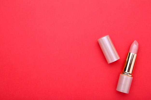 Lápiz labial desnudo sobre fondo rojo, de cerca