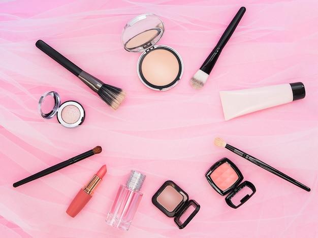 Lápiz labial, herramientas, delineador de ojos, rubor, perfume, sombra de ojos y polvos cosméticos en color rosa con maquillaje en el marco para la promoción.