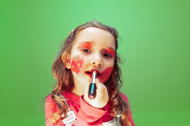 Lápiz labial. niña soñando con la profesión de maquillador. concepto de infancia, planificación, educación y sueño. quiere convertirse en un empleado exitoso en la industria de la moda y el estilo, artista de peinado.