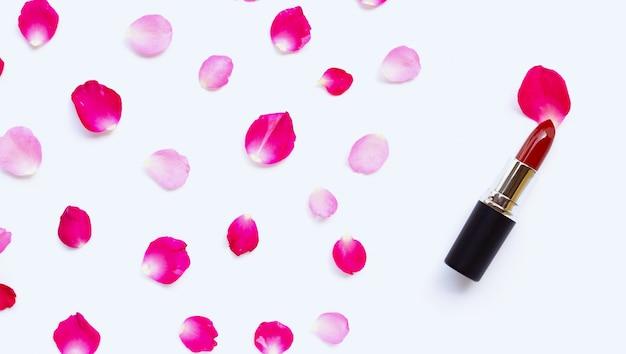 Lápiz labial con pétalos de rosa aislado sobre fondo blanco.