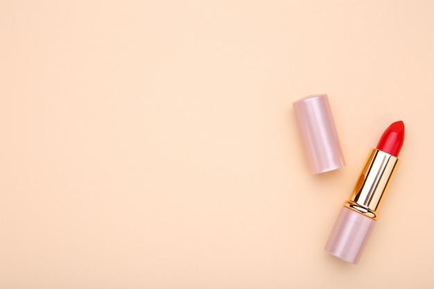 Lápiz labial rojo sobre fondo beige, maquillaje