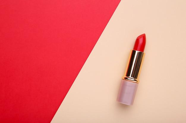 Lápiz labial rojo sobre fondo colorido, de cerca