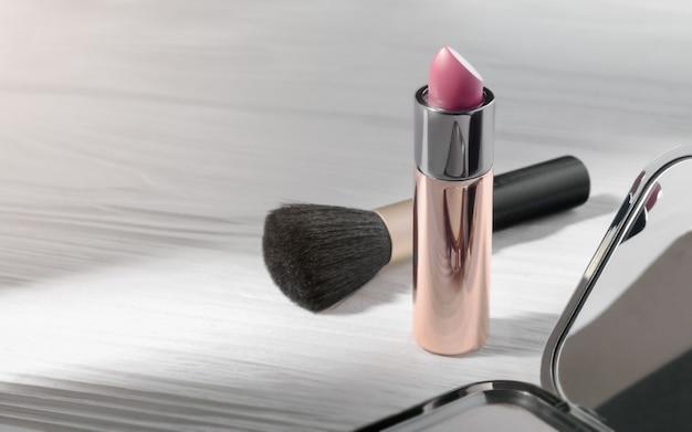 Lápiz labial rosa y pincel sobre mesa de madera blanca - maquillaje sobre madera