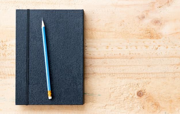 Lápiz y libro puestos en la mesa.