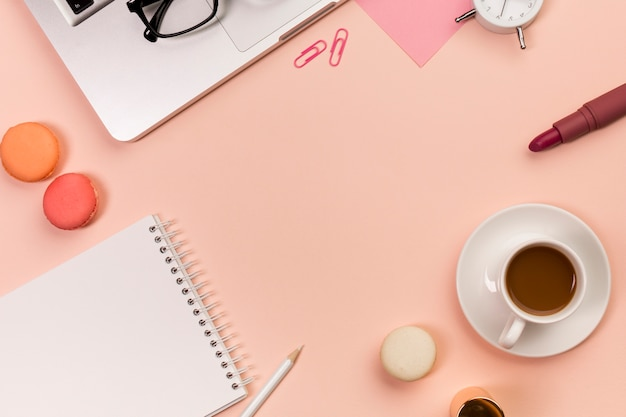 Lápiz, macarrones, bloc de notas en espiral, taza de café, lápiz labial, lentes en la computadora portátil sobre el fondo color melocotón