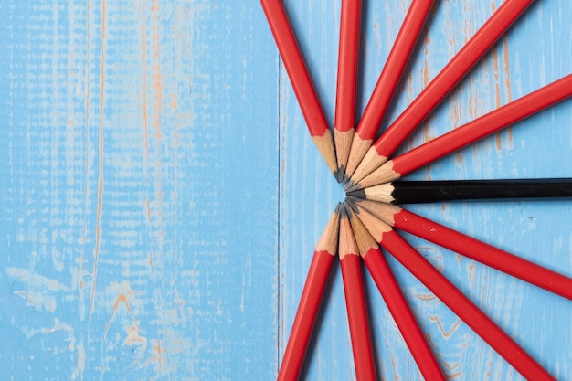 Lápiz negro y lápices rojos sobre fondo azul de madera.