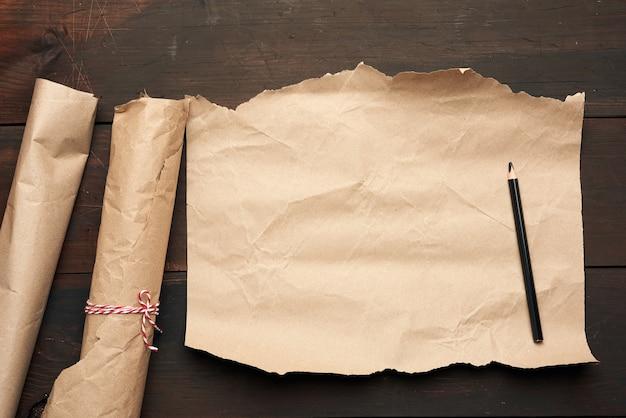 Lápiz negro y rollo de papel marrón sin retorcer sobre una superficie de madera de tableros viejos