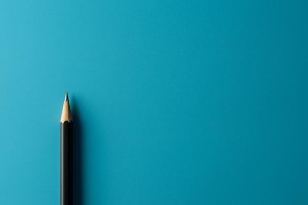 Lápiz negro sobre fondo de papel azul. - concepto de negocio.