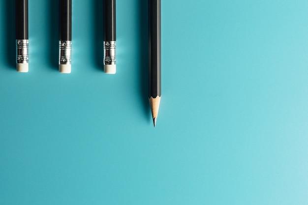 Lápiz negro sobre fondo de papel azul