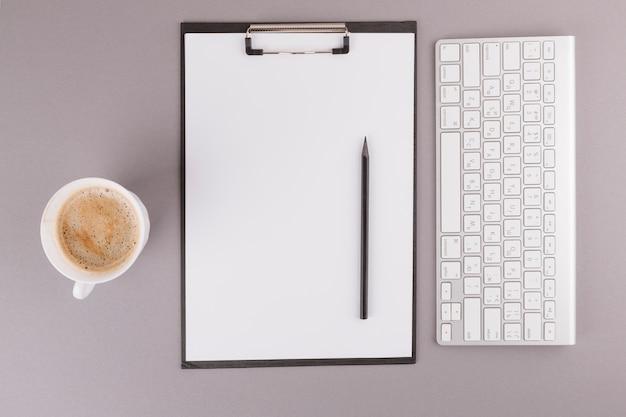 Lápiz y papel en el portapapeles cerca del teclado y la taza