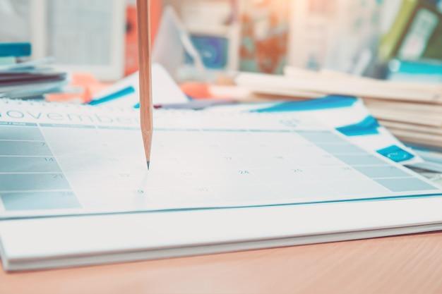 Lápiz de primer plano en el calendario de escritorio en blanco