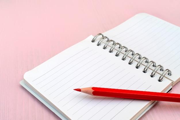 Lápiz rojo y cuaderno de notas.
