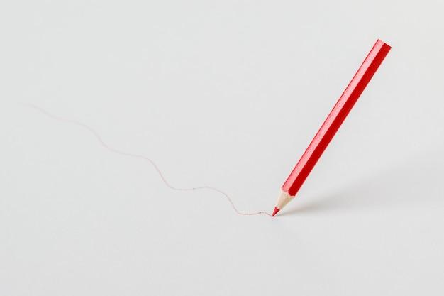 Lápiz rojo dibujando una línea sobre un fondo blanco. papelería y útiles escolares.