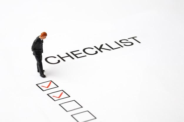Lápiz rojo marcado en la casilla de lista de verificación con hombre de negocios en miniatura