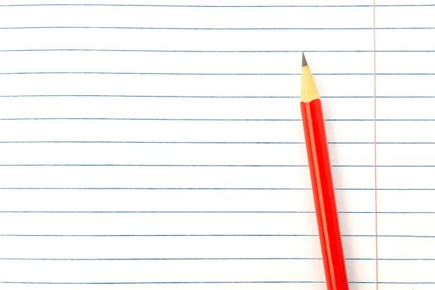 Lápiz rojo en primer plano de fondo de libro, maqueta, espacio de copia