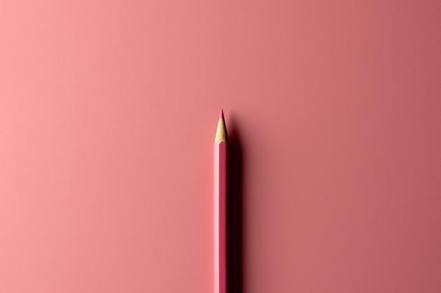 Lápiz rosado del creyón en el fondo de papel rosado
