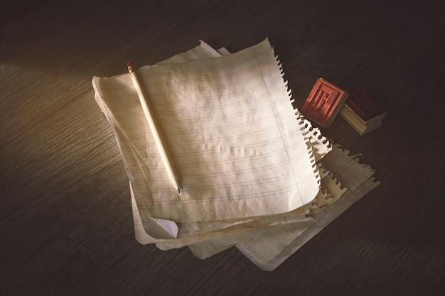 Lápiz y sellos cerca de hojas de papel antiguas