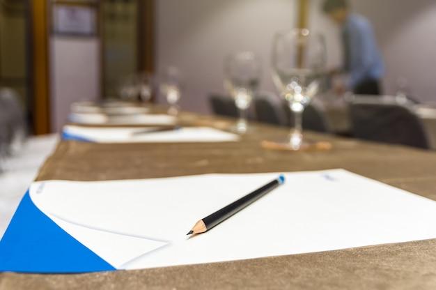 Lápiz sobre el papel en la mesa de trabajo con vaso de agua en el seminario