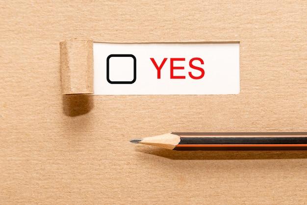 Lápiz sobre papel rasgado con el texto escrito sí y una casilla de verificación. concepto de toma de decisiones