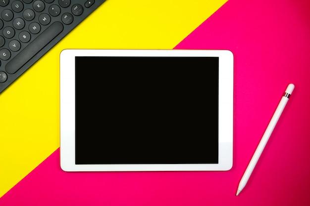 El lápiz y el teclado de la tableta en el fondo dos entonan con el espacio amarillo y rosado de la copia para el texto