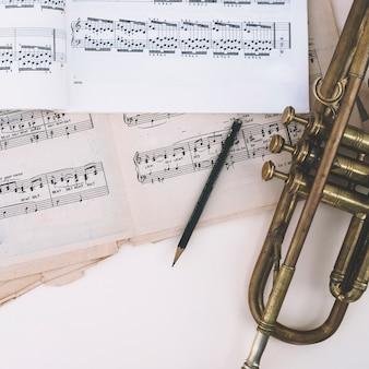 Lápiz y trompeta cerca de partituras